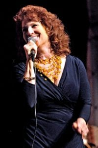 Picture of Pamela Rose singing with a microphone