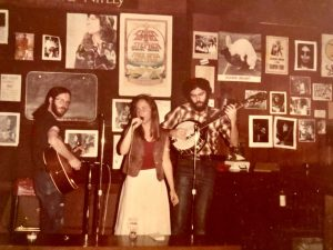 Mary singing in a band, early in her career. Shown in a cafe with a guitarist and a banjo player.