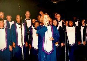 Mary singing solo on stage, on microphone with the Oakland Interfaith Gospel Choir