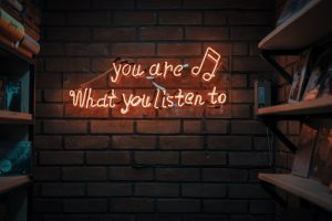 Picture of a lit up sign that reads: you are what you listen to